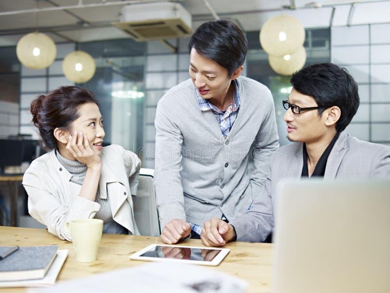 Jeunes entrepreneurs asiatiques discutant des affaires dans le bureau image libre de droits