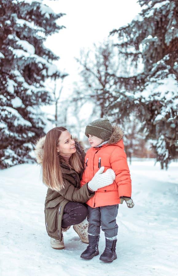 Jeunes entretiens d'une mère à son fils, un petit garçon de 3-5 années Hiver dans les bois à l'air frais Émotions de joie photographie stock