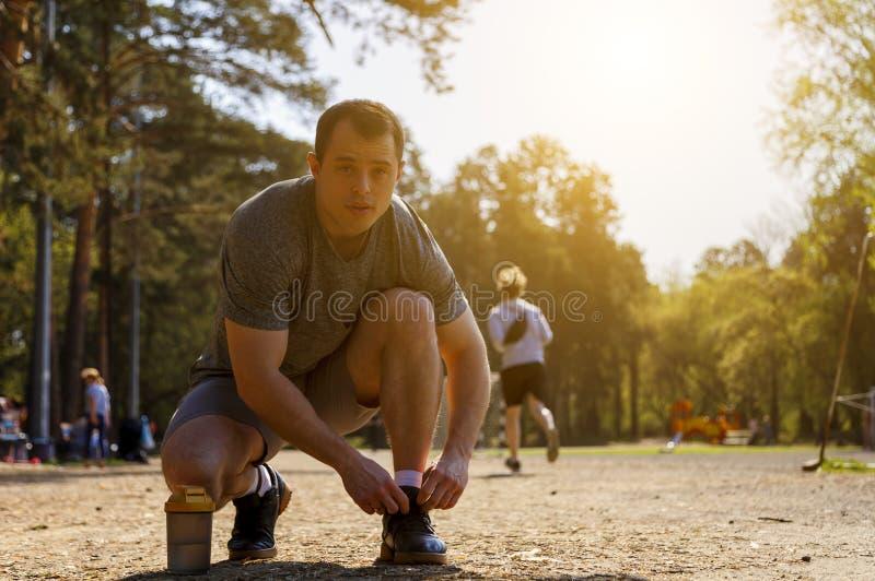 Jeunes espadrilles caucasiennes sérieuses de laçage de sportif se tenant sur le genou photo stock