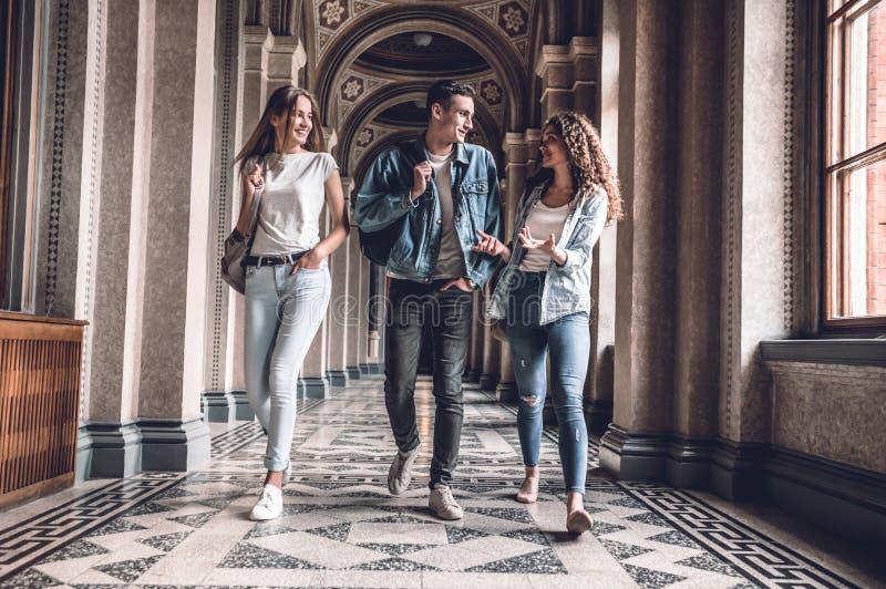 Jeunes et beau Le groupe d'étudiants sûrs marchent dans l'université, la causerie et le sourire photos stock
