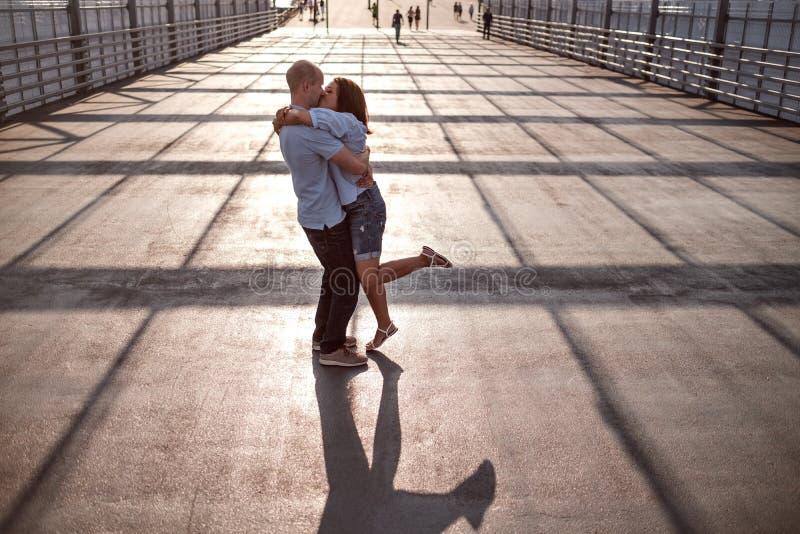 Jeunes et beaux couples embrassant sur la rue sur la lumière et les ombres du bâtiment image stock