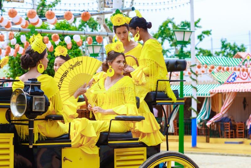 Jeunes et belles femmes sur un chariot hippomobile pendant l'April Fair de Séville images stock