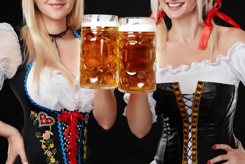 Jeunes et belles filles bavaroises avec deux tasses de bière sur le fond noir photos stock