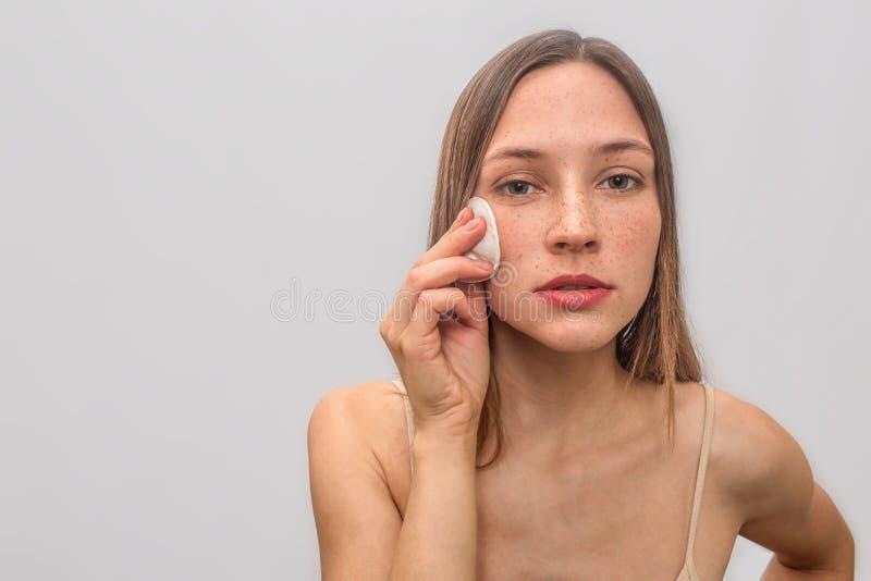 Jeunes et couverts de taches de rousseur supports et regards de femme sur la caméra Elle tient l'éponge de coton avec la main sur photographie stock libre de droits