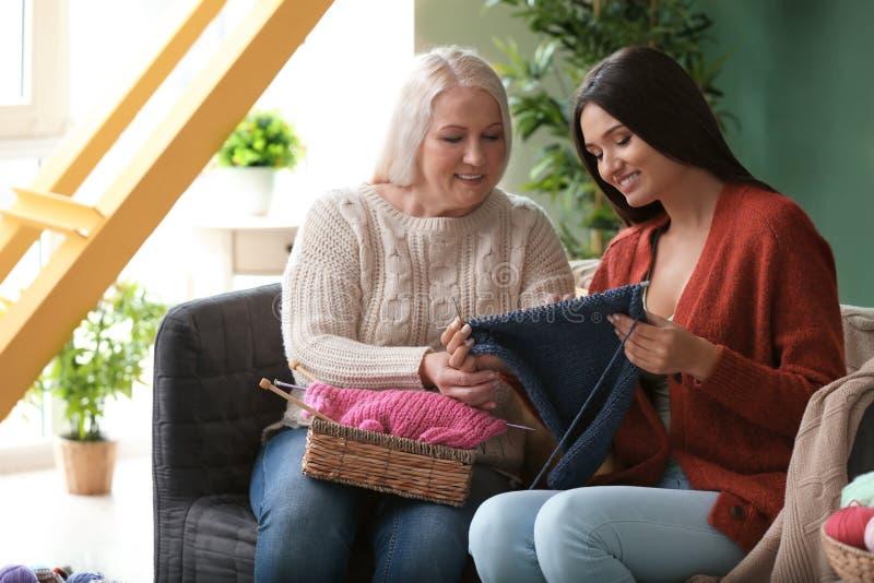 Jeunes et mûres femmes avec le fil à tricoter se reposant sur le sofa à l'intérieur image stock