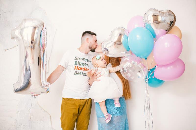 Jeunes famille, parents maman et papa embrassant et tenant le bébé un an sur un fond blanc à la maison Le concept d'un enfant photo stock
