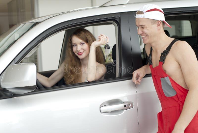 Jeunes femme et homme de sourire près de véhicule photo stock