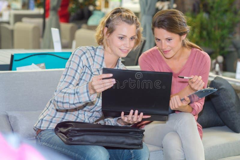 Jeunes femmes à l'aide de l'ordinateur portable sur le sofa image libre de droits