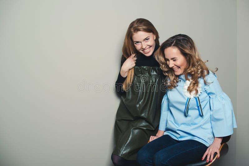 Jeunes femmes à la mode enthousiastes ayant l'amusement ensemble Deux meilleurs amis mignons de filles souriant et embrassant Par images stock