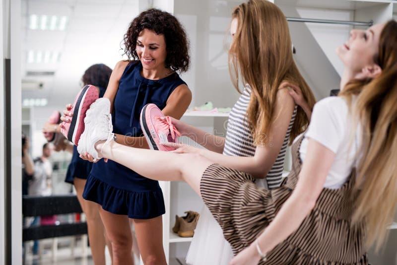 Jeunes femmes aidant leur ami à choisir des chaussures de sports comparant les semelles de nouvelles et vieilles chaussures dans  photo stock