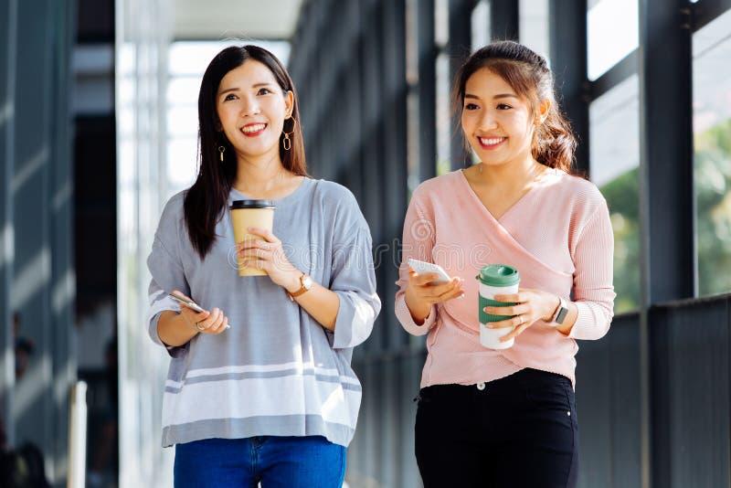 Jeunes femmes asiatiques d'affaires parlant tout en marchant dans l'immeuble de bureaux dans la tenue de détente photographie stock