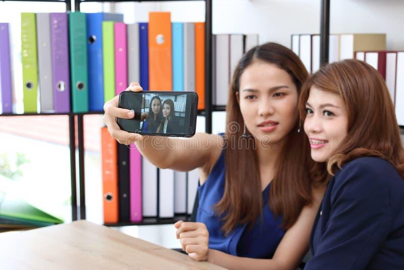 Jeunes femmes asiatiques de sourire d'affaires prenant une photo ou un selfie ensemble dans le bureau photographie stock