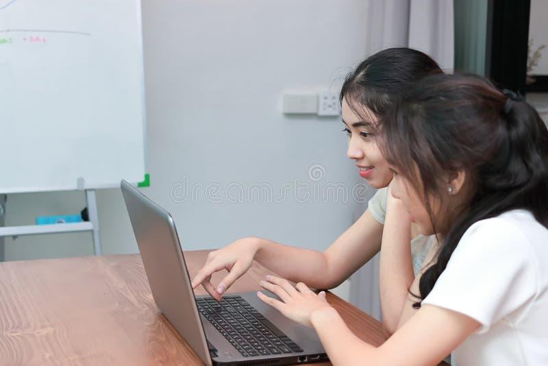 Jeunes femmes asiatiques gaies avec l'ordinateur portable faisant des emplettes en ligne ensemble images stock