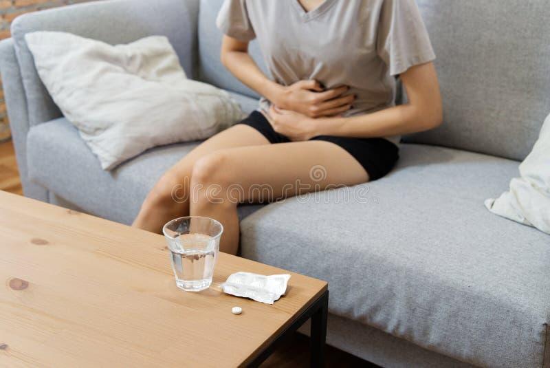 Jeunes femmes asiatiques sur la douleur de sofa du mal de ventre et avoir une certaine fièvre en raison des règles image stock