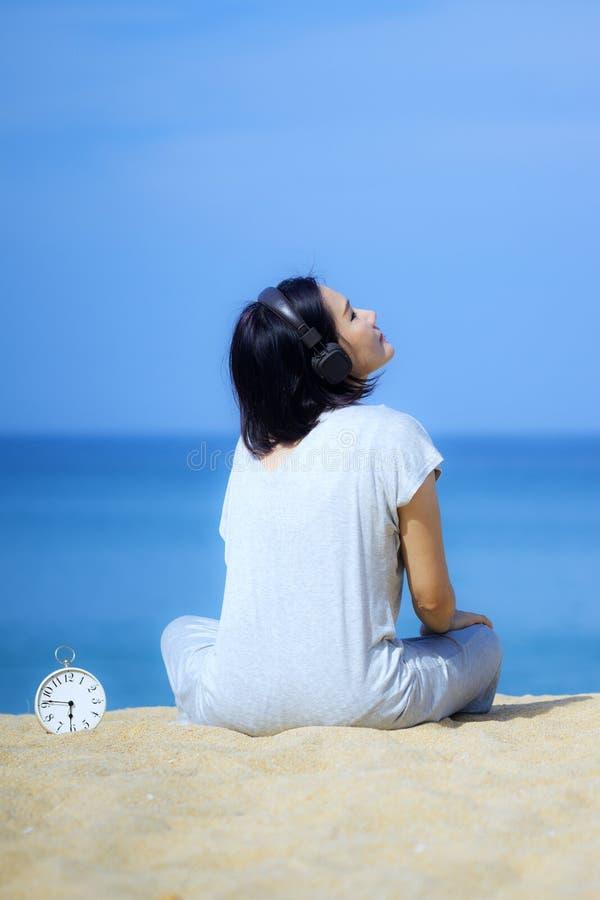 Jeunes femmes asiatiques utilisant des écouteurs, écoutant la musique à la plage Réveil blanc placé sur le sable Mer et ciel bleu photographie stock libre de droits