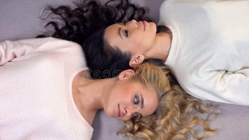 Jeunes femmes attirantes avec de beaux longs cheveux se trouvant sur le plancher, séance photos photos stock