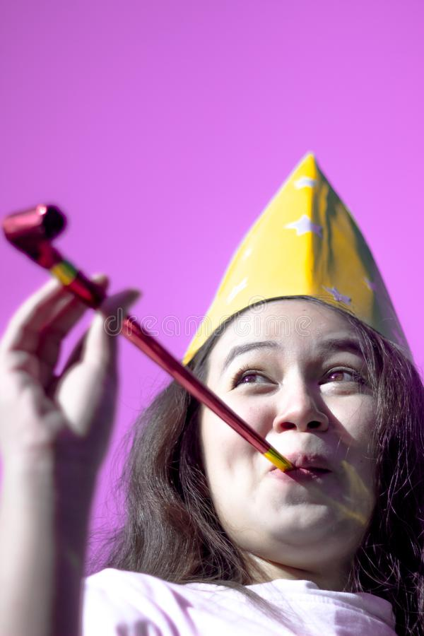 Jeunes femmes attirantes utilisant le chapeau de partie encourageant et célébrant le klaxon de soufflement de partie Belle fille  photos libres de droits