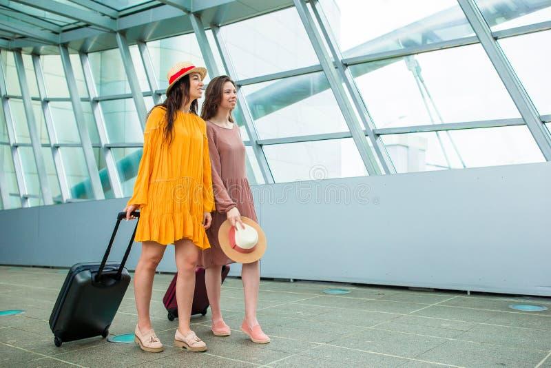 Jeunes femmes avec des sacs dans des avions de attente de vol d'aéroport international images libres de droits