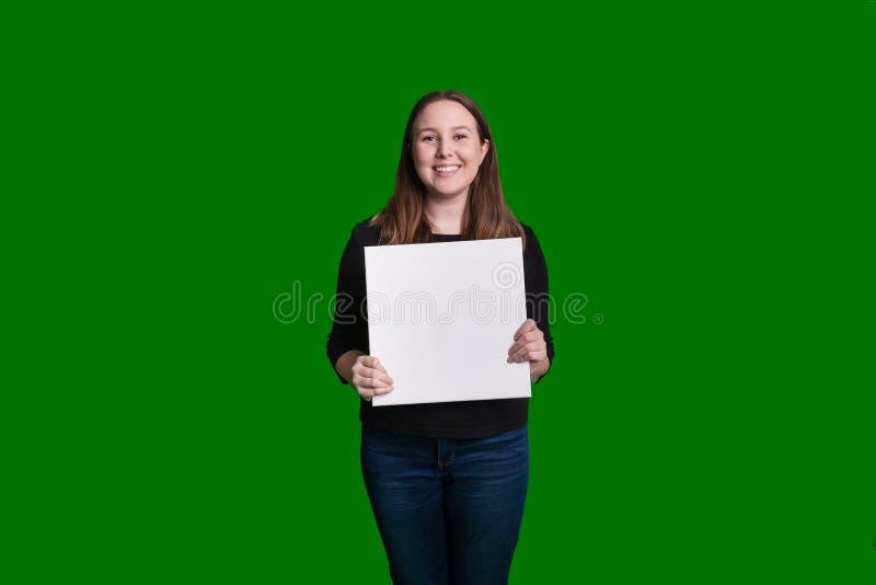 Jeunes femmes blondes jugeant le signe vide de tableau blanc devant elle sourire capturé sur le contexte vert d'écran photos stock