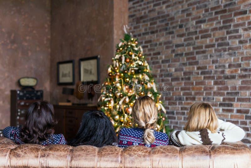 Jeunes femmes causant tout en se reposant sur le sofa près de l'arbre de Noël photos stock