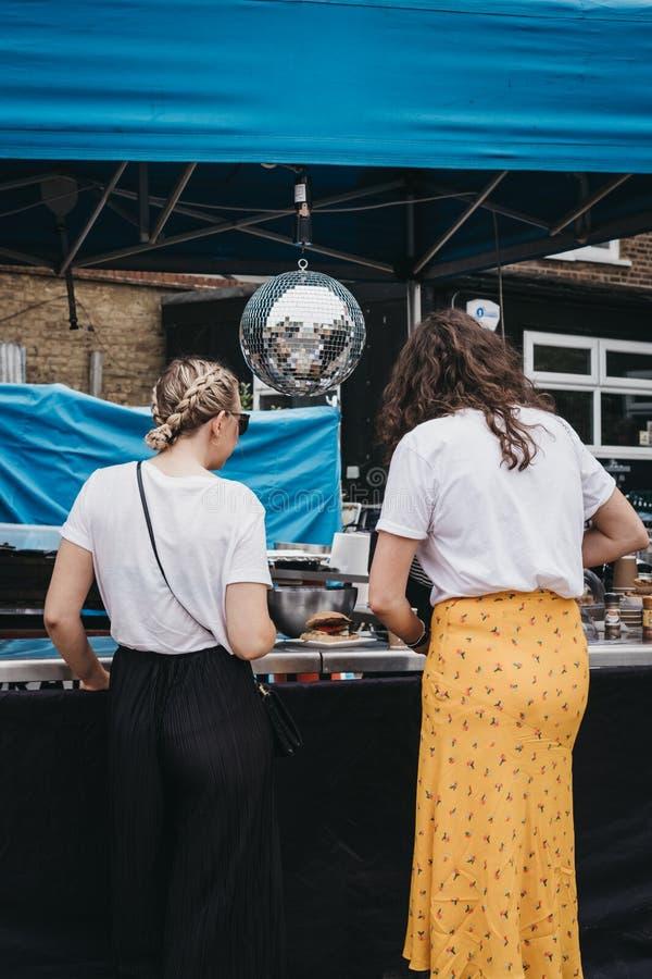 Jeunes femmes commandant la nourriture d'une stalle du marché sur la rue d'Erza, Londres, R-U image libre de droits