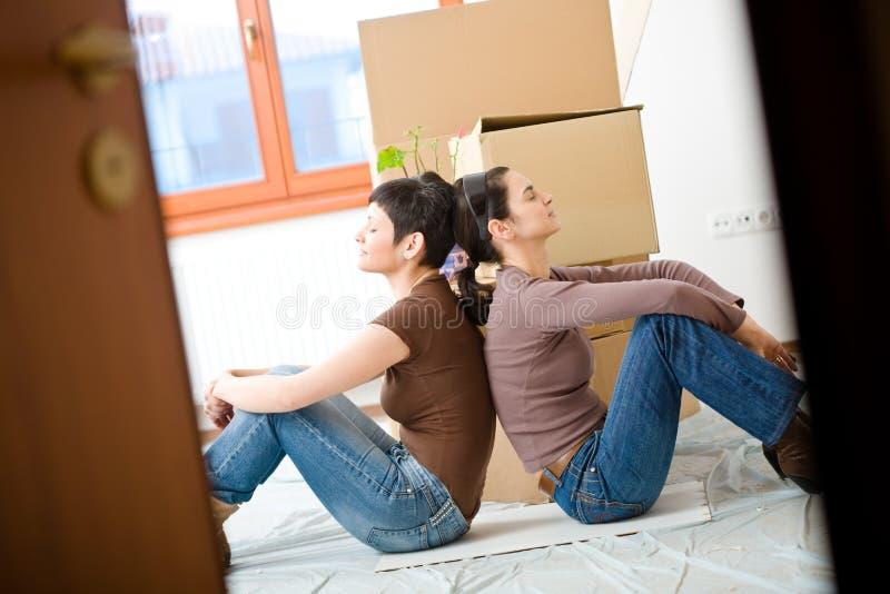 Jeunes femmes déménageant à la maison photo stock