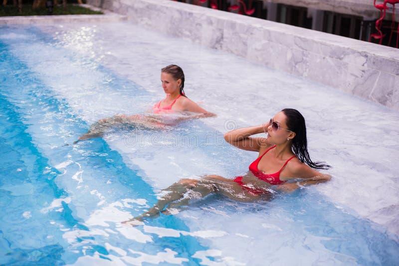 Jeunes femmes détendant par la piscine photo libre de droits
