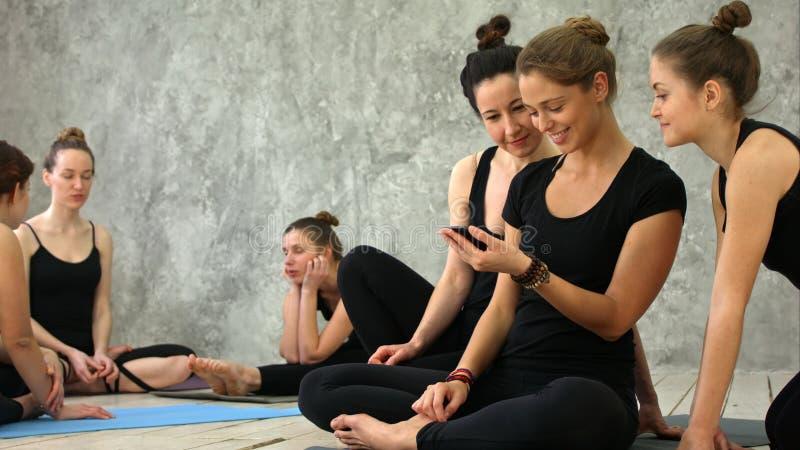 Jeunes femmes détendant, utilisant le smartphone, parlant après séance d'entraînement à la classe de yoga photographie stock libre de droits