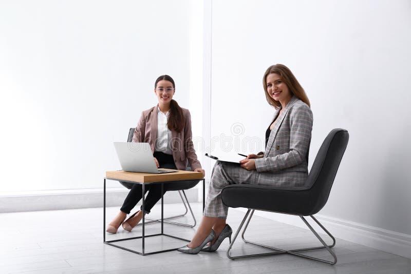 Jeunes femmes d'affaires assises à table dans des fauteuils photographie stock libre de droits