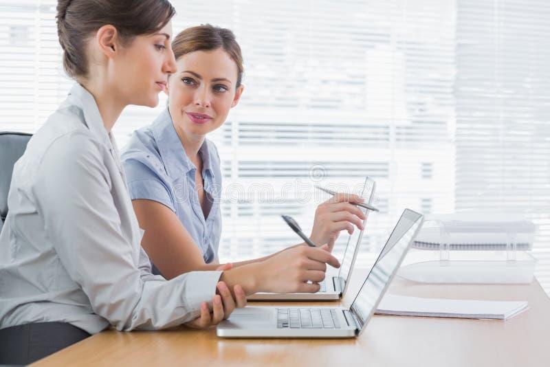 Jeunes femmes d'affaires travaillant ensemble sur leurs ordinateurs portables photo stock