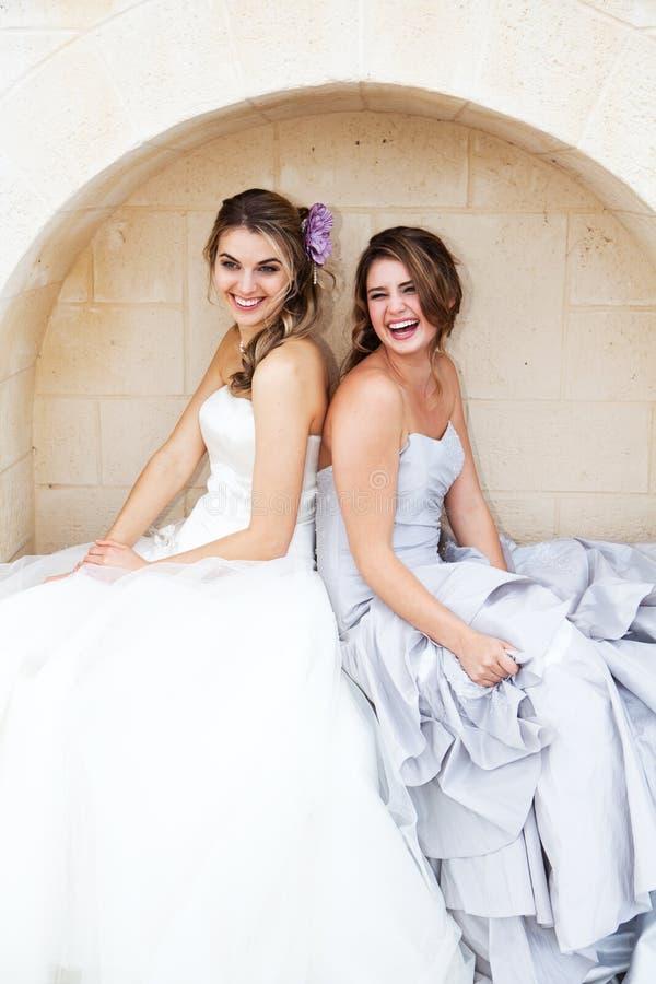 Jeunes femmes dans des robes et se reposer dans une chambrette images stock