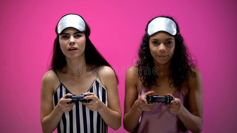 Jeunes femmes dans l'usage de sommeil tenant des manettes et jouant le jeu vid?o, ?motions photographie stock
