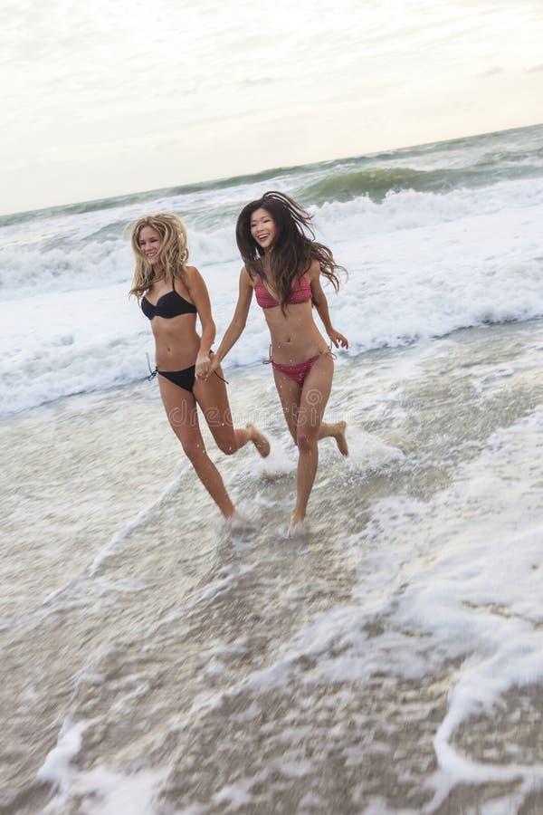 Jeunes femmes de filles dans des bikinis fonctionnant sur la plage images libres de droits