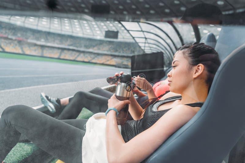 Jeunes femmes de forme physique dans les vêtements de sport se reposant dans des sièges de stade images stock