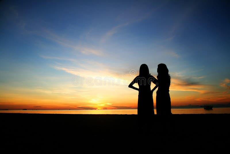 Jeunes femmes de silhouette sur la plage image libre de droits