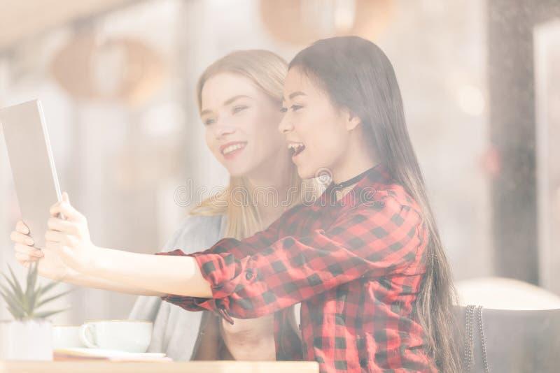 Jeunes femmes de sourire buvant le café et employer le café numérique de comprimé ensemble photo libre de droits