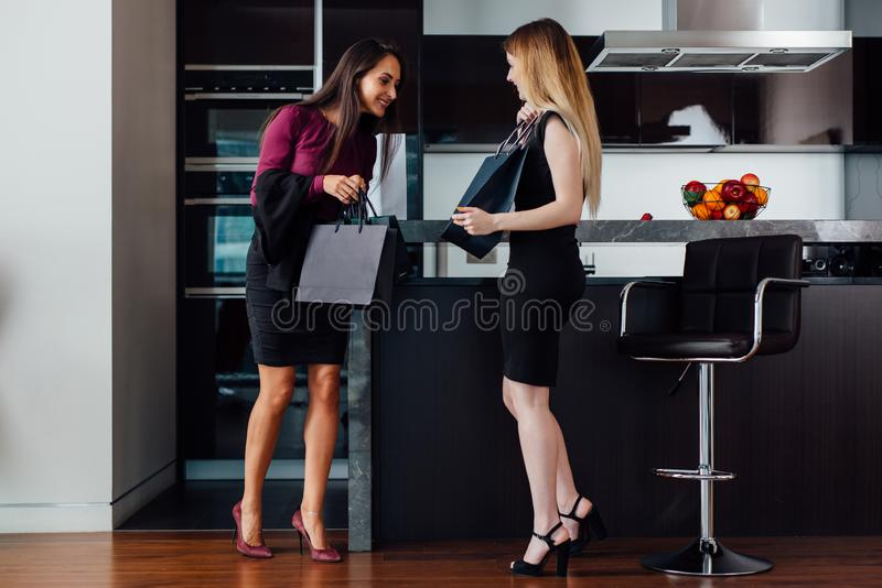 Jeunes femmes de sourire portant les vêtements élégants formels regardant dans le panier se tenant dans l'appartement moderne image stock
