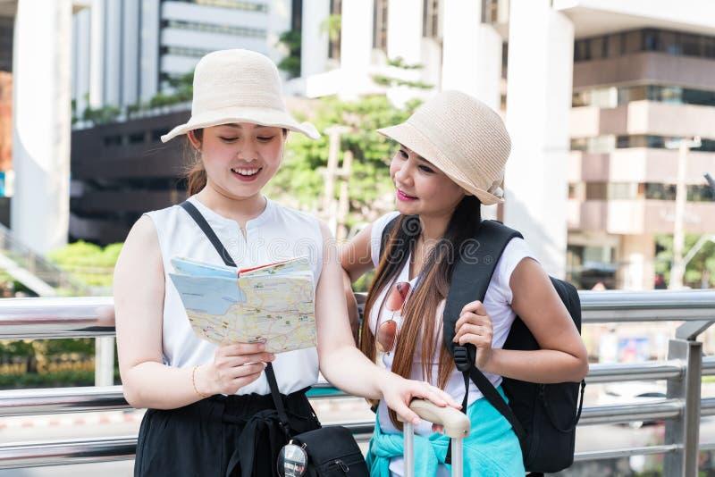 Jeunes femmes de touristes asiatiques utilisant des chapeaux recherchant la direction d'une carte avec les visages de sourire photos stock