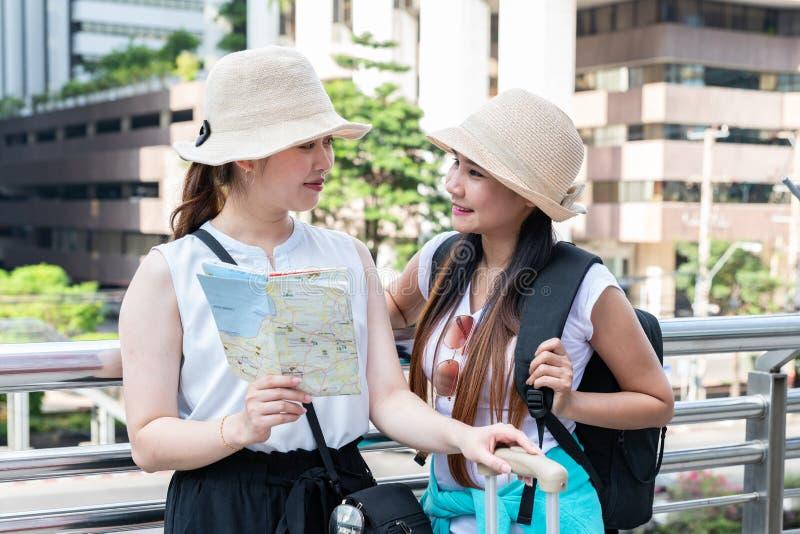 Jeunes femmes de touristes asiatiques utilisant des chapeaux regardant l'un l'autre avec les visages de sourire images stock