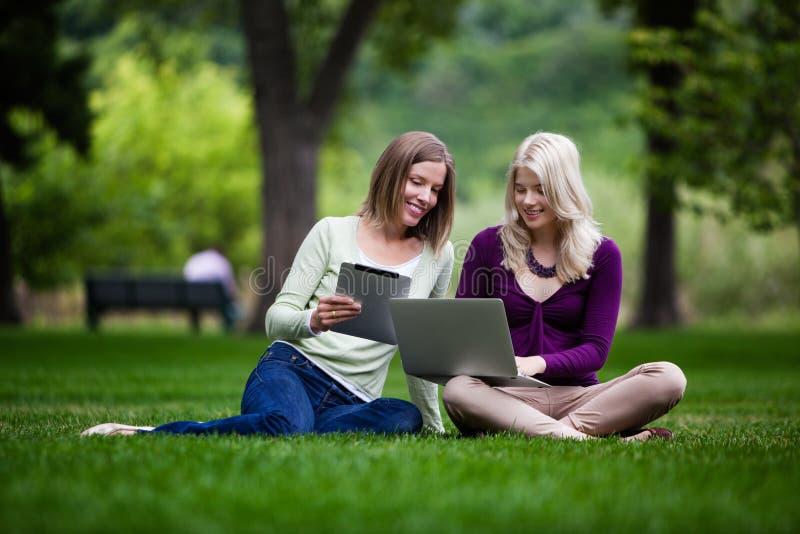 Jeunes femmes en parc avec la technologie photos stock