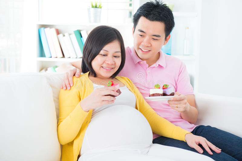 Femme enceinte d'Asiatique mangeant le gâteau photographie stock libre de droits