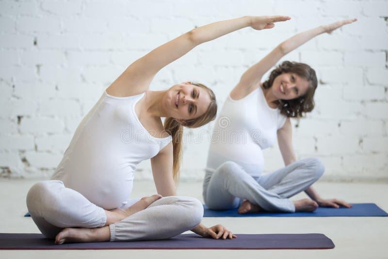 Jeunes femmes enceintes faisant le yoga prénatal Recourbement dans la pose facile photo stock