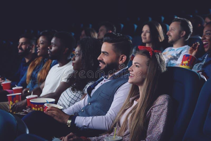 Jeunes femmes et hommes passant le temps gratuit dans le cinéma ensemble images stock
