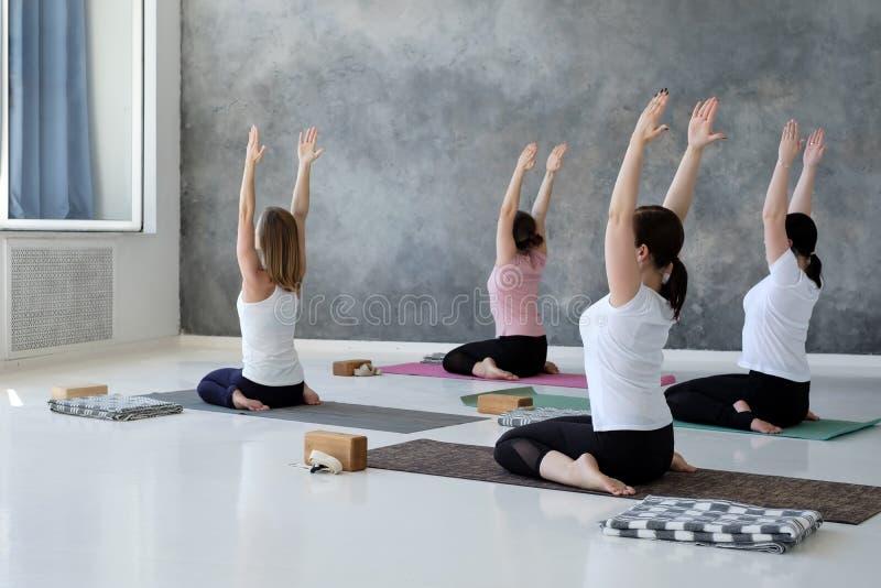 Jeunes femmes faisant l'exercice de yoga, se situant dans la pose de héros, Virasana photos stock