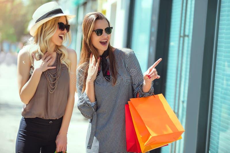 Jeunes femmes heureuses avec des paniers indiquant le doigt la fenêtre de boutique images libres de droits