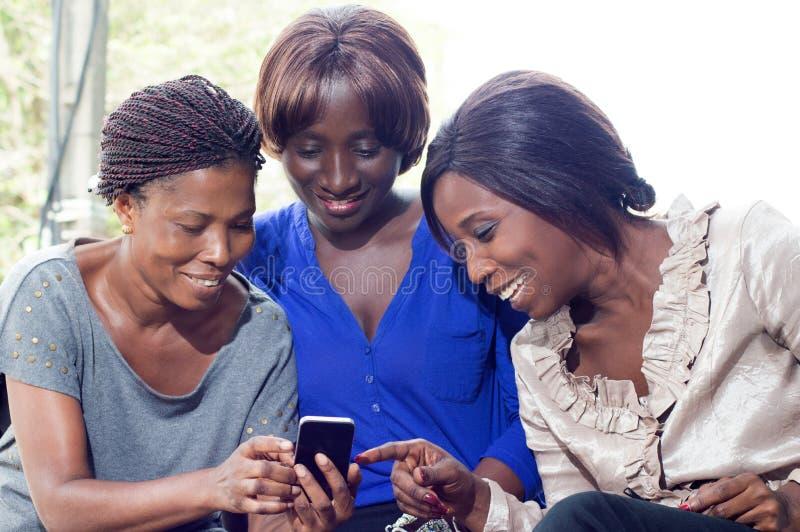 Jeunes femmes heureuses de découvrir la technologie mobile photographie stock libre de droits
