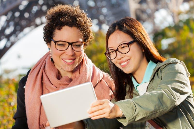 Jeunes femmes heureuses prenant la photo de selfie avec le comprimé photos stock