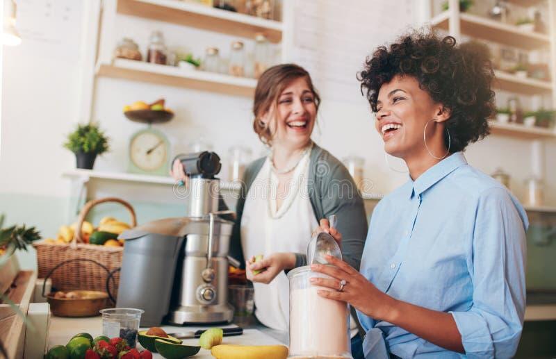 Jeunes femmes heureuses travaillant au compteur de bar à jus photos stock
