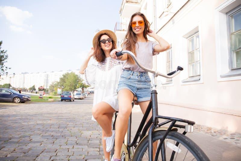 Jeunes femmes joyeuses montant une bicyclette ensemble Meilleurs amis ayant l'amusement sur un vélo à la promenade de rivière dan photographie stock libre de droits