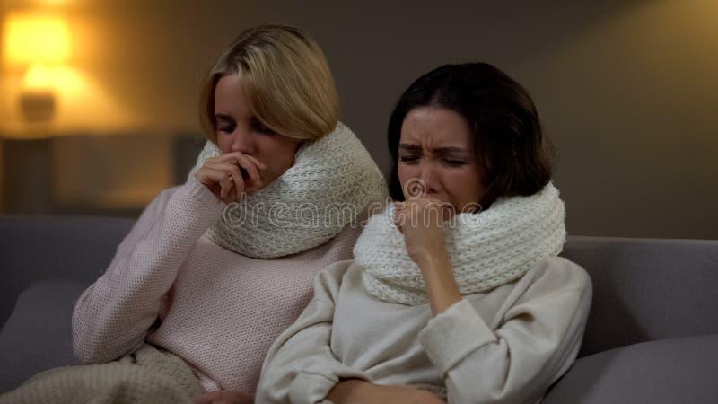 Jeunes femmes malades dans des ?charpes se situant dans le lit et toussant, virus de grippe, quarantaine photo stock